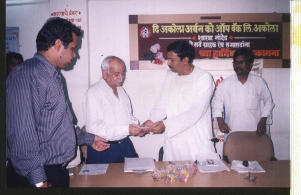 Handing over eye donor card to director of Akola urban bank