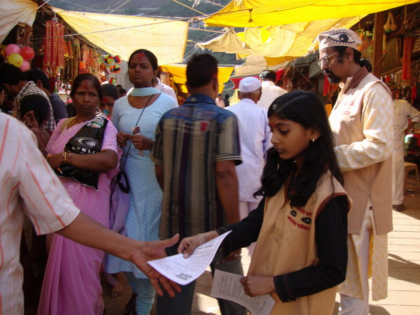 Disha soni and Ad. Kishor Soni distributing pamphlets about eye donation in the crowdy area of temple at vani